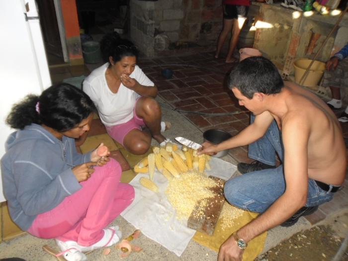 algunos vecinos preparando el arroz amarillo con maíz