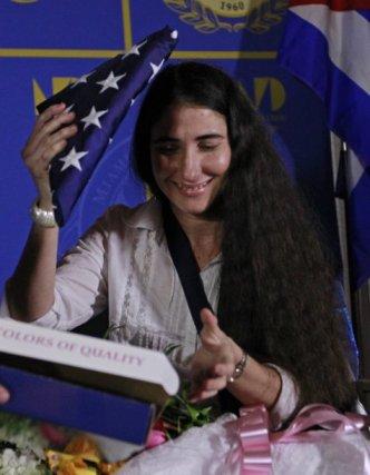 Yoani usa, adorando la bandera de quienes le pagan