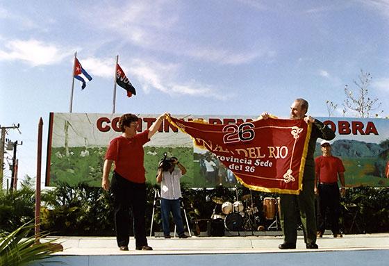 Fidel Castro Ruz en el momento en que entrega a María del Carmen Concepción González, Primera Secretaria del PCC en la provincia, la bandera por la sede del acto nacional por el 26 de Julio el 5-8-2000